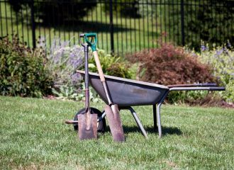 Landscapers in Montgomery, AL - Pair of shovels resting against a wheelbarrow in a flower filled backyard